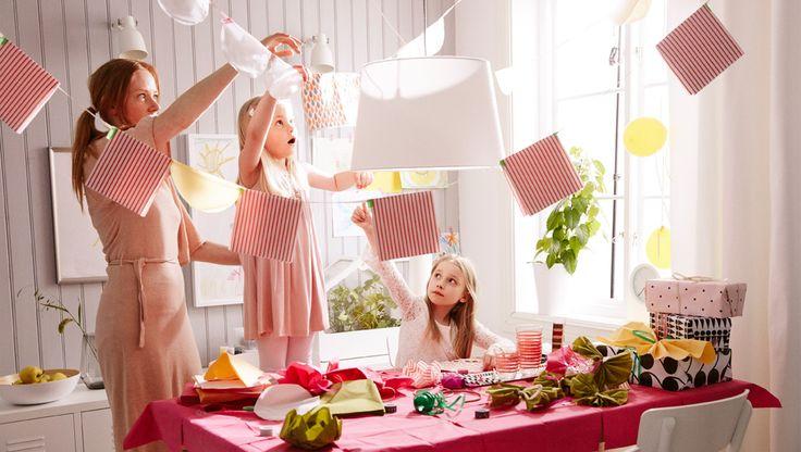 Мама и двое детей украшают стол цветными бумажными салфетками.