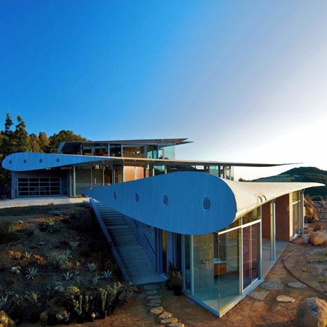 The suspended wings rest over self-supporting glass walls that front the hillside house, which was designed by American architects Studio of Environmental Architecture.