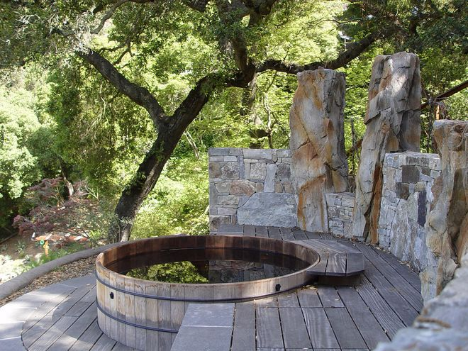 hot tub and rustic deck with stone surround, I'd prefer it without the stone pillars