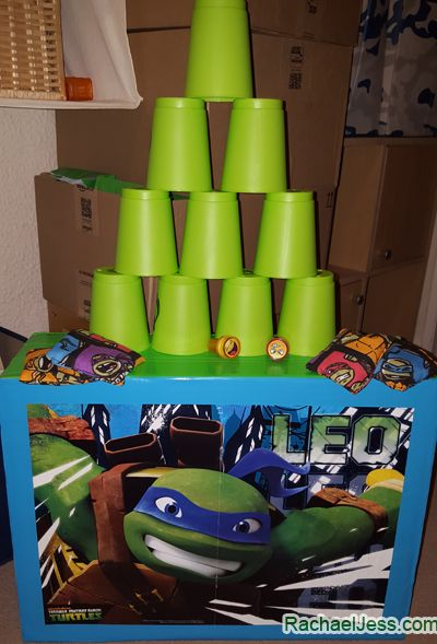 groene bekers op elkaar stapelen en met een softbal proberen de toren in zo weinig mogelijk beurten om te gooien