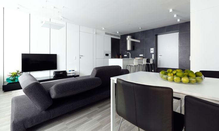 Obklad pôsobí exkluzívnejšie a je odolnejší ako obyčajná biela stierka, preto sme ho navrhli na všetky steny v dennej časti. Na obývačkovej stene je obklad z bielych panelov s integrovanými dverami do spálne, ktorý prechádza do kuchynských skriniek. Vstupná a kuchynská časť sú obložené šedým gresovým obkladom.