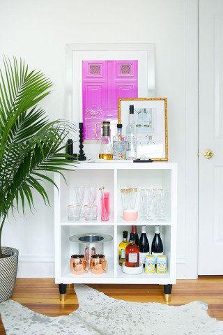 Os copos, taças e garrafas organizados nas quatro divisões enfeitam o cantinho do estar
