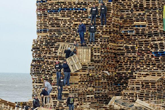 Op het Scheveningse strand wordt hard gewerkt aan de vuurstapels voor het Oud en Nieuwfeest. Duizenden pallets worden opeen gestapeld voor een groot vreugdevuur. Foto's: Phil Nijhuis / Hollandse Hoogte