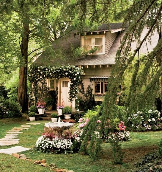 Darling house with arch of roses over front porch.  Love it!