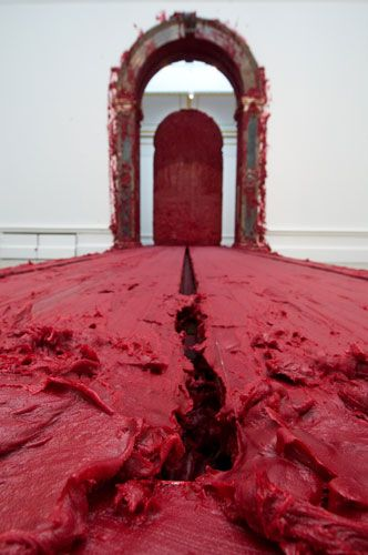 """Anish Kapoor, """"Svayambh"""". The mobile centrepiece is a massive moving block of red wax. Its title comes from the Sanskrit word meaning """"self-generated""""."""
