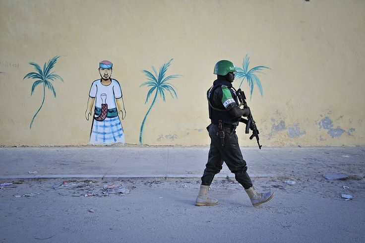 A Nigerian policeman walks by a newly built wall on a foot patrol near Lido beach in Somalia's capital, Mogadishu. As part of AMISOM's efforts to make Mogadishu a safer place, regular foot patrols are now conducted throughout the city by the mission's Formed Police Units (FPUs). AU-UN IST PHOTO / TOBIN JONES.