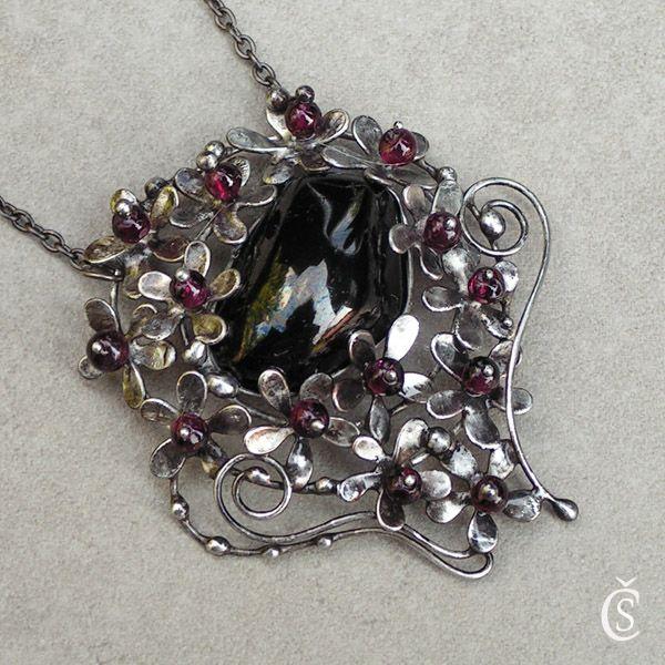 """Celý v květu - Gagát, Granát Originální Autorský šperk """"Celý v květu - Gagát, Granát"""" POPIS:Ústředním kamenem tohoto šperku je černý, zcela hladký Gagát, jemuž se také říká """"černý jantar"""". Jako by sám rozkvetl, je obklopen spoustou drobných kvítků, které mají ve svém středu malé korálky Granátku. Korálky krásně prosvítají vínovou barvou (viz. foto). ..."""