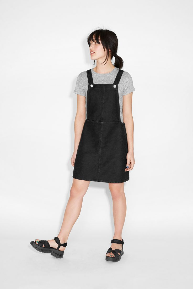 Sweet denim salvation is knowing you have this black dungaree dress hanging around! Styled up so easily with a slight kick-out skirt (zip closure), and adjustable straps with trademark Monki Denim buttons all matte'd out.  colour: black magic  In a size38 the waist width is 83,5 cm. The model is 170 cm and is wearing a size 38.