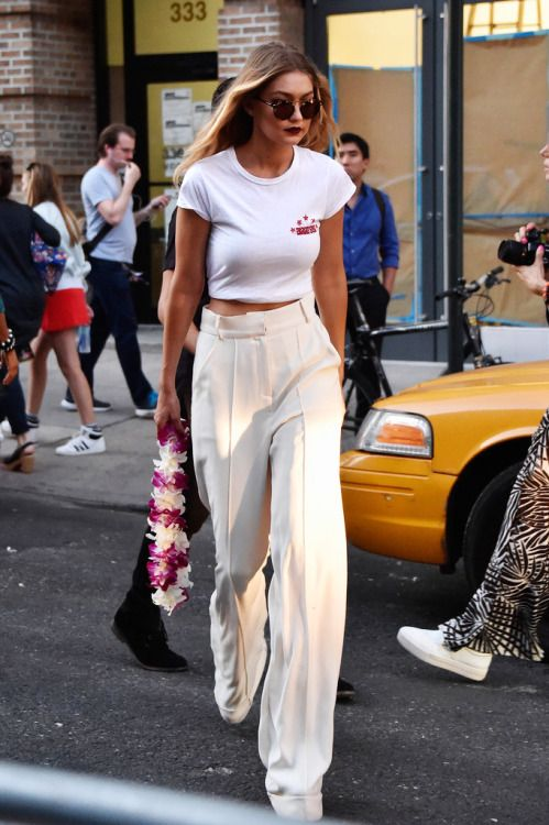 Gigi Hadid in a retro white tee and high-waist cream trousers with a vampy lip