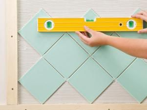 Follow these easy step-by-step instructions on how to properly measure and cut curves and holes in tile. Plus, find out how to lay tile in a diamond pattern and how to create borders.