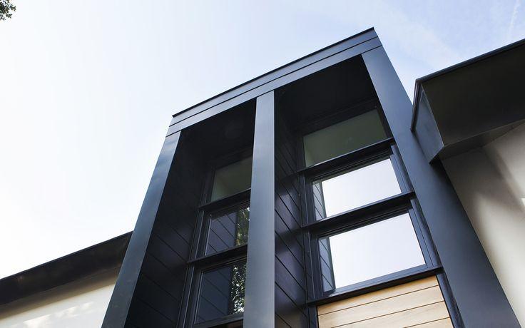 eigentijdse woning | Een moderne, wit gestucte woning op De Scheifelaar voorzien van een imposante entree, donkere overstekken, donkere vlakke dakpannen en diepzwarte horizontaal gelede kozijnen. De woning is sfeervol gelegen en georiënteerd op het buitengebied.