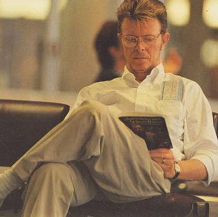 He waits for his flight. Damn..... reading is SO sexy........