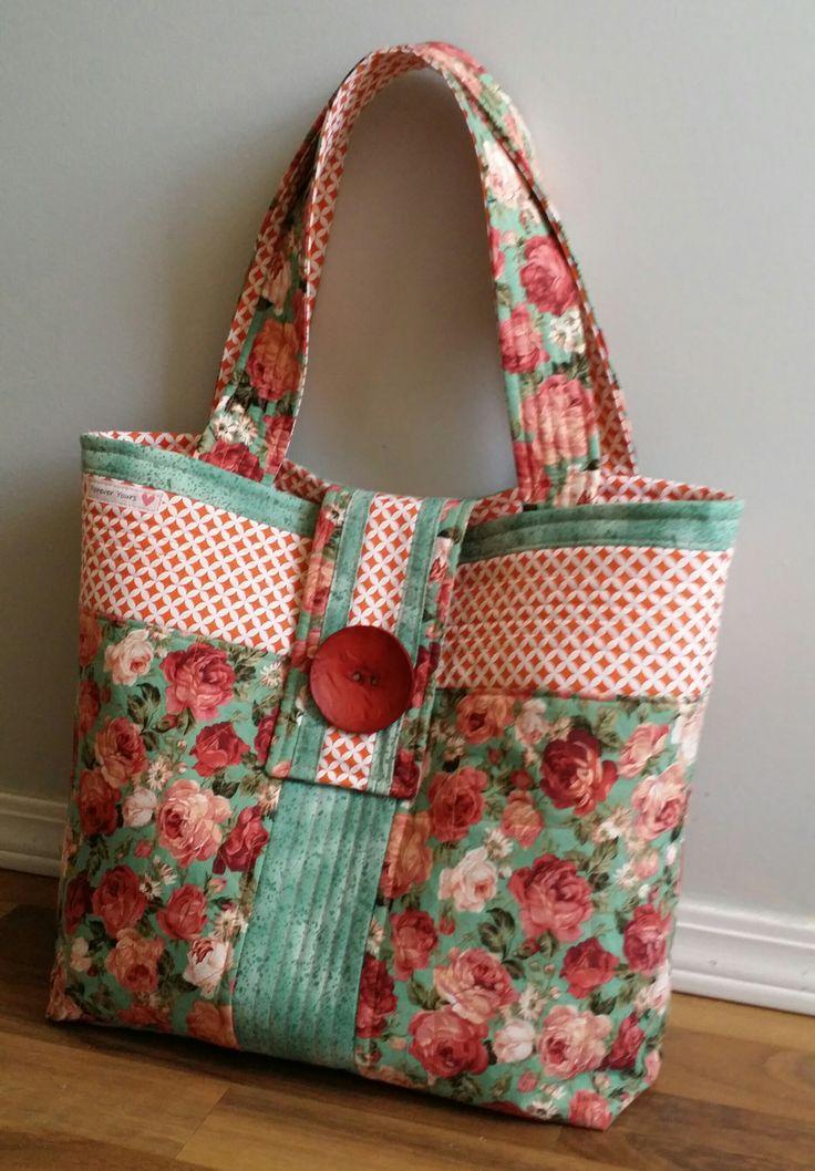 Bolsa con tela de flores rojas, verde, con botón.