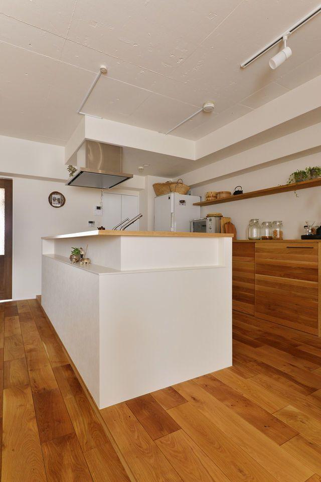 K邸、マンションリノベーション事例。余白をデザインする。キッチンは回遊できるよう配置し、家事動線をスムーズにしました。キッチンカウンターのデザインは、だんな様のアイデアでアシンメトリーにしています。キッチン後ろの家電収納は造作。扉はフローリング材を利用して木のぬくもりが感じられるようにしています。TV台と本棚は、ツーバイ材で造作し、壁面は珪藻土をご夫妻でDIYされました。キッチンを移動させるにあたって、勾配をとる為の床段差を空間のアクセントにしています。