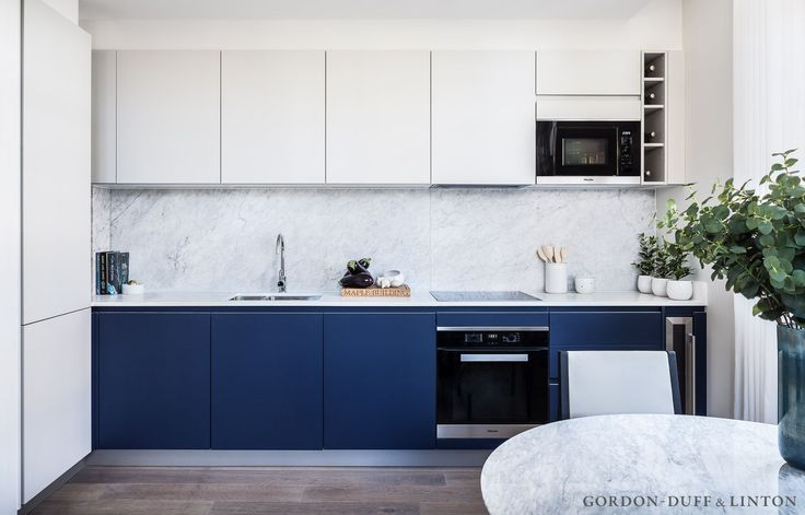 Blue and off-white kitchen with Miele appliances and full-height carrara marble splashback. Saarinen marble dining table and two-tone leather and dark wood chairs.