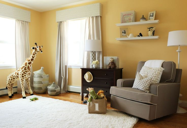 Super cute gender neutral nursery in soft yellow and yellow with dark contrasts in the arm chair and dresser.