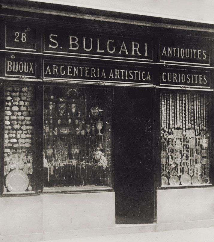 Front of Bulgari's second Roman shop at 28 Via dei Condotti, photographed around 1900. The sign reads: ''S.Bulgari - Argenteria Artistica, Antiquités, Curiosités, Bijoux''. The windows, crammed with great variety of silver objects, also display numerous belt buckles - typical ornaments of Sotirio's production at that time. Photo © Bulgari Archives.
