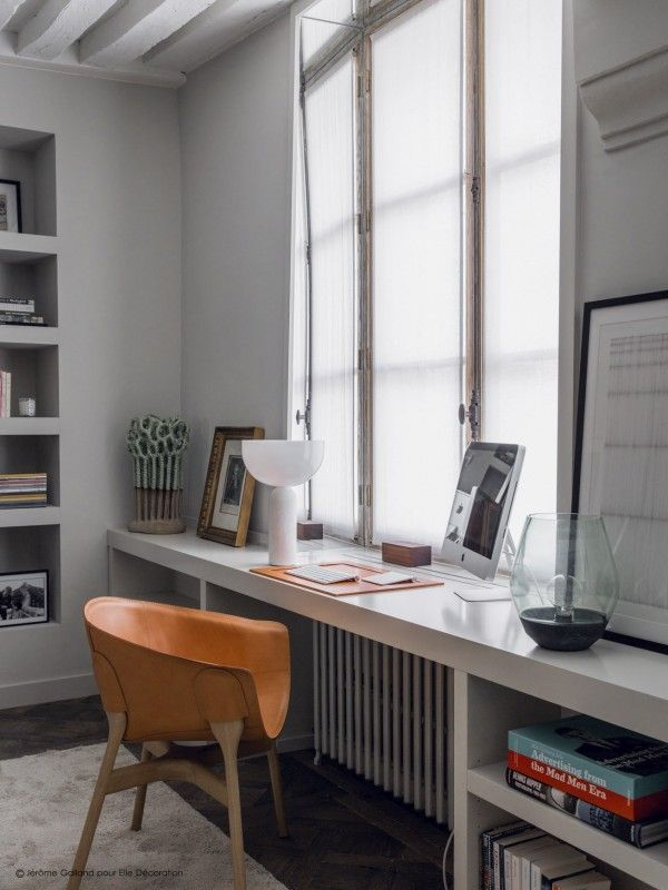 Home offices can exist in small apartments. A simple shelf and a mid-century chair make a fun and functional workspace