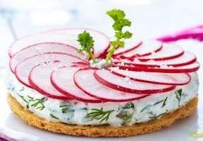 Piquez la pâte brisée et découpez 4 disques de 10 cm de diamètre. Enfournez à 180°c pendant 20 min environ. Mélangez au fromage frais les câpres, les cornichons, les échalotes, les herbes fraîches et l'œuf dur. Nettoyez et coupez les radis avec une mandoline. Masquez à l'aide d'une cuillère les disques de pâte puis rangez harmonieusement les tranches de radis. Servez avec un trait de vinaigrette et quelques herbes et fleurs.   Accompagnée d'une salade verte et d'un rosé frais, c'est un…