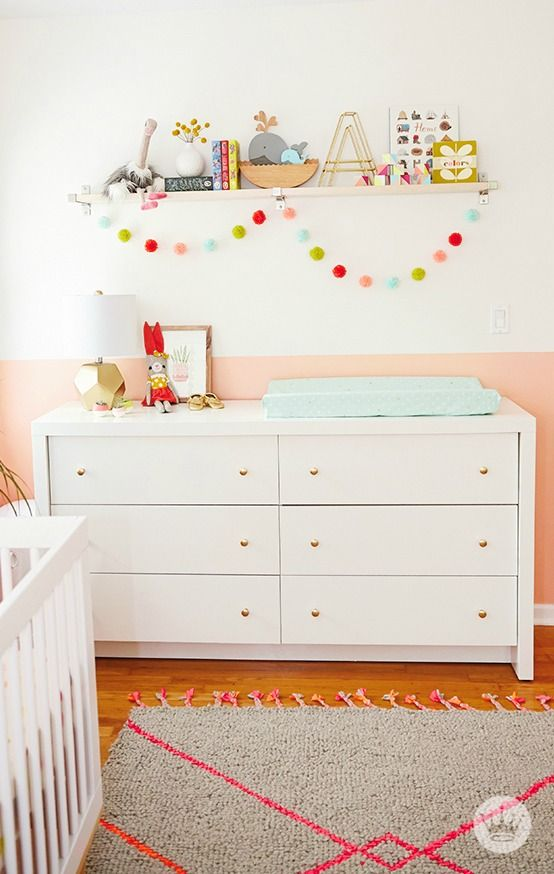 Soft pink shades paired with pops of color and playful accessories are the key to creating the perfect baby girl nursery. Add some fun shelving accessories and a cozy rug to her space—we love this DIY pom pom garland that really brings happy vibes into the room!