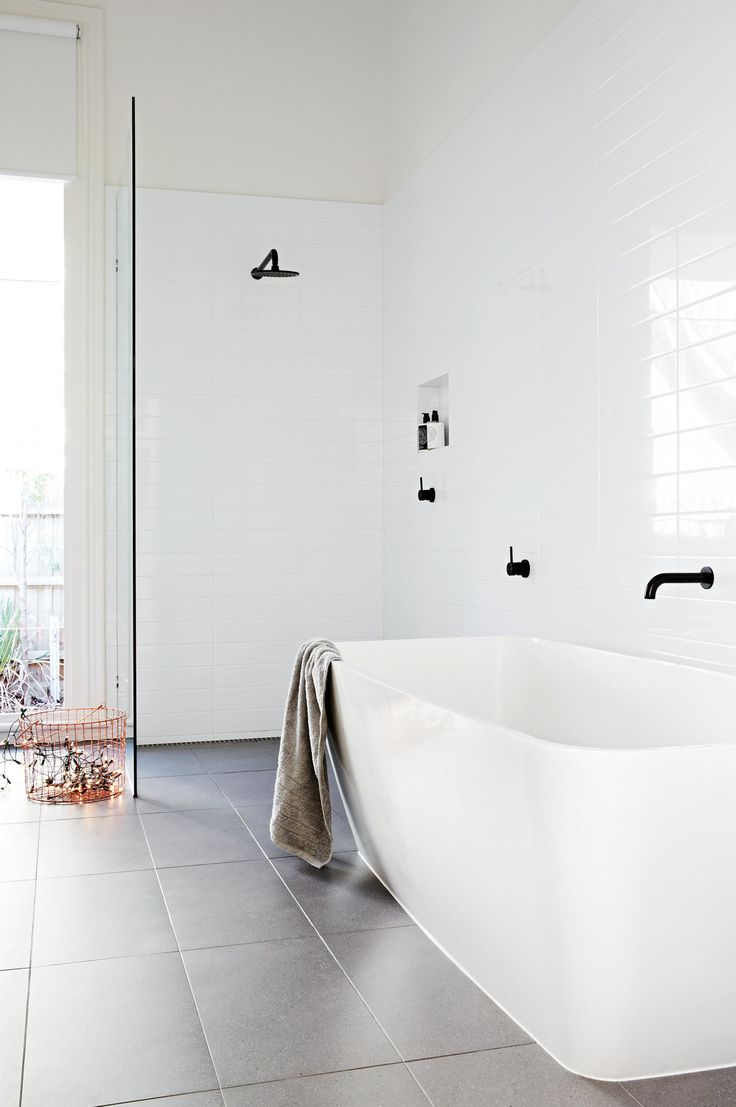 the choice of black tapware gives this glossy white bathroom a subtle but dynamic edge grey floor tiles add warmth and depth to the space photographer