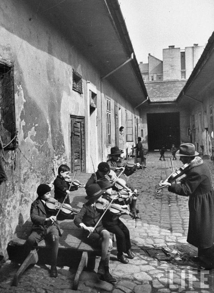 Cigánygyerekek hegedülni tanulnak egy 8. kerületi lakóház udvarán. (1939) forrás: time.com