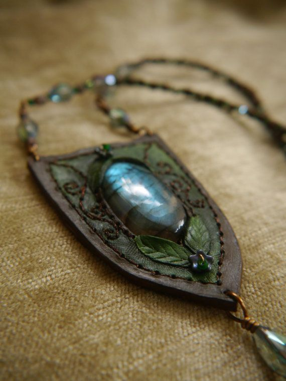 leather and labradorite pendant necklaces - this one is themed around enchanted woodlands, with a gorgeous flashing labradorite in shades of teal green surrounded with a hand made leather shield shaped frame with leaves tooled on. Ive added a graded green background and dark brown border, with hand embroidered shimmering bronze brown spirals and tiny glass flowers, and then finished the whole thing with a hand made bronze coloured wire and crystal charm. The necklace it h...
