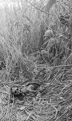 Hill 110 and a Marine of 1/26th beside the decomposed body of N.V.A. soldier, hidden in tall elephant grass near Nghi Thong City. - Vietnam War