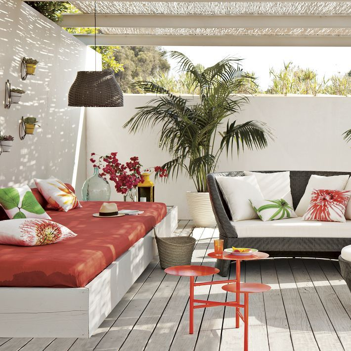 This pretty patio says Florida to me. A simple outdoor setting all in white made pretty with salmon & floral pillows and mats.