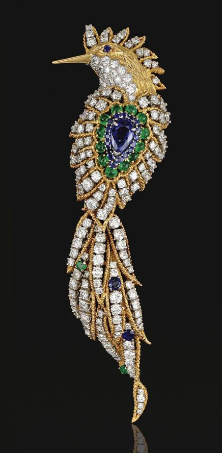 SAPPHIRE, EMERALD AND DIAMOND BROOCH, VAN CLEEF & ARPELS.  Designed as a bird of paradise set throughout with brilliant-cut diamonds within gold corded wire surrounds, the body centring on a pear-shaped sapphire, bordered by circular-cut similar stones, to the cabochon emerald outline, the removable tail randomly set with circular-cut emeralds and sapphires, mounted in platinum and yellow gold,  signed V.C.A. N.Y. and numbered.