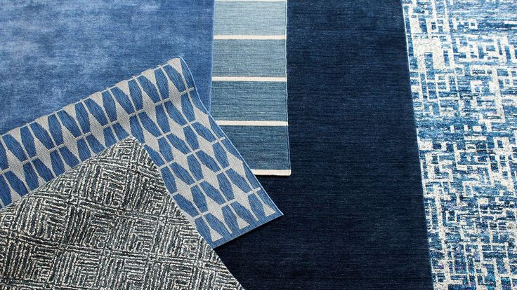 A variety blue patterned rugs layered on top of each other. Shop blue trend.
