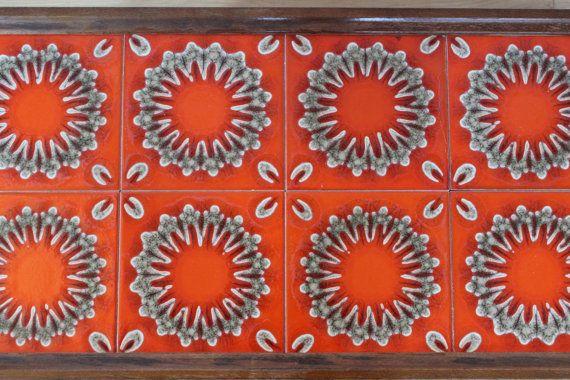 Schöne Blumenbank aus den 70er Jahren. Das Tischgestell ist komplett aus Holz und die Tischplatte besteht aus 8 Kacheln in den für dieses Jahrzehnt typischen Farben. Ein schönes Objekt als Beistelltisch, Blumentisch oder kleiner Kaffeetisch nutzbar.  Der Tisch ist in einem guten Vintagezustand. Kacheln sind unbeschädigt. Kleine altersentsprechende Abnutzungen am Holzgestell, s.Fotos.  Maße: Höhe ca. 32 cm | 12.59 inch Größe Tischplatte: 64 cm x 34 cm | 25.19 inch x 13.38 inch Gewicht ca…