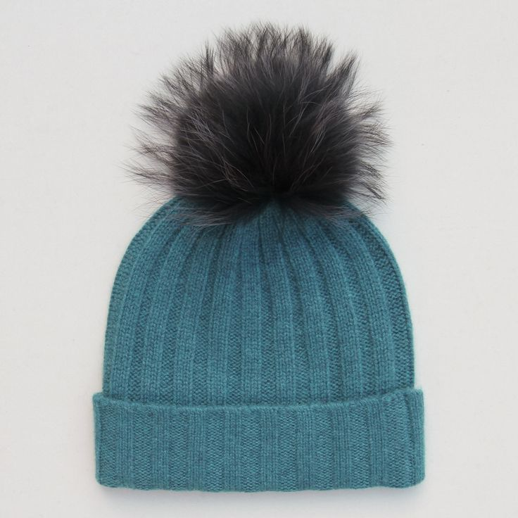 Luxurious and warm this fluffy pom pom cashmere bobble hat is perfect for the autumn and winter months. Made from 100% cashmere the black fur pom pom looks great against the teal ribbed knit hat. The fur bobble is attached by a button and can be removed for washing. Why not change up your look with any of our separate fur pom pom attachments.