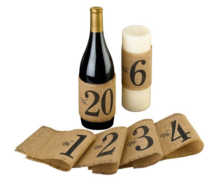 """These burlap table number wraps are an excellent alternative to traditional table numbers. Use them on a wine bottle or candle to create the perfect stylish centerpiece and help your guests find their tables with ease. The wraps measure 14"""" long and 3.75"""" wide. Numbers 1-20 are included."""