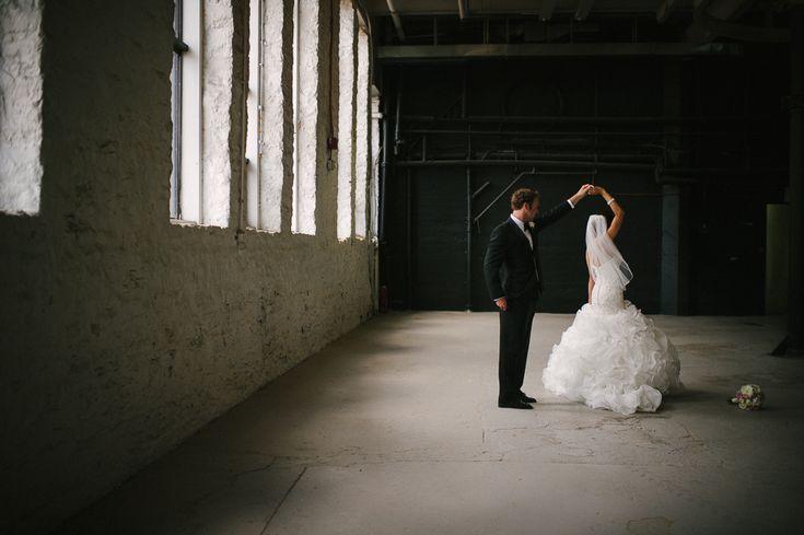 bride and groom dancing in warehouse