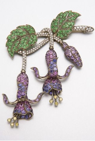 18K GOLD, SAPPHIRE, DIAMOND AND GREEN GARNET BROOCH 108 diamonds approx 1.00 ct, 3 sapphires missing.