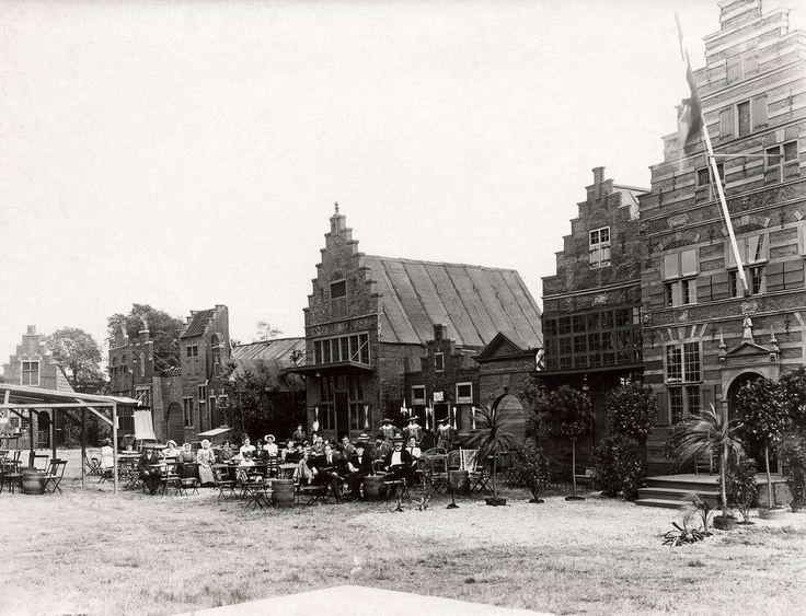 Steden en dorpen. Feestelijkheden in Laren(N-H). In het dorp is een decor van historische huizen opgebouwd. Ervóor op het grasveld zitten volwassenen en een paar kinderen op een terrasje. Laren, 1914 #Laren #Gooi #NoordHolland #vierkant