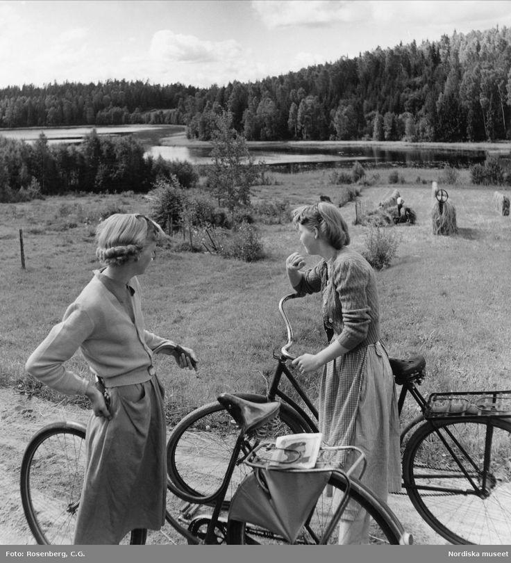 Två flickor med cyklar på landsväg. I bakgrunden pågår höbärgning. Fotograf Rosenberg, C.G.
