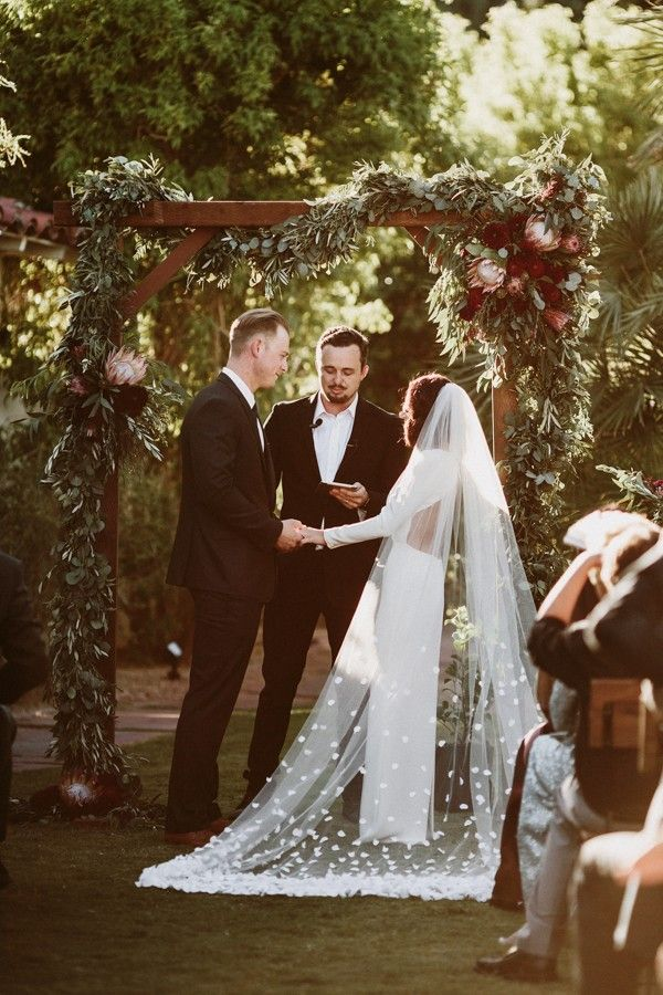 Gorgeous wooden arch with stunning vines & pink proteas | Image by Lauren Scotti Photography