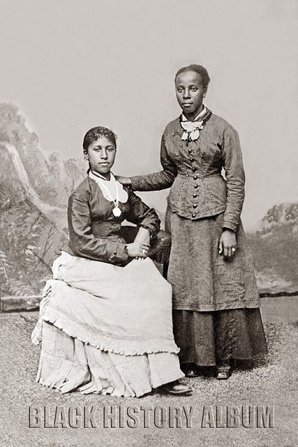 Portrait of two young African American women, one standing, one seated. Hand-colored tintype, circa 1890s.