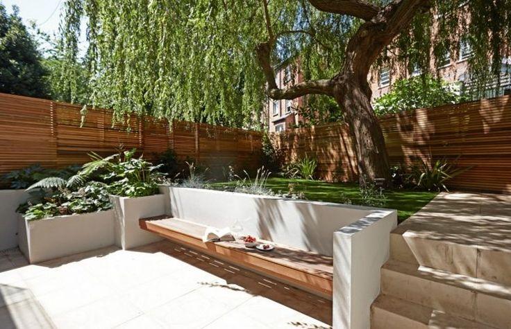 gemauerte Sitzbank im Halbschatten des Weidenbaums