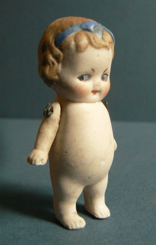 Antique bisque Kewpie-esque doll, eBay. If this weren't someone else's photo, I'd use the doll's face for my profile picture here or somewhere. :)