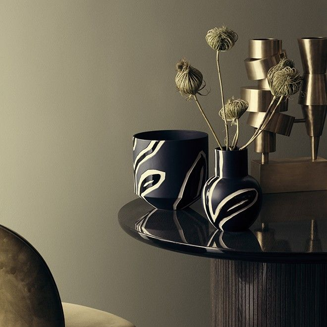 The midnight blue Fiora vase belongs to the darker colour spectrum of the Fiora range, where a creamy white and a touch of gold form a contrast to the dominant midnight blue colour. Add depth and warmth to your decor with this midnight blue vase, beautifully embellished with the characteristic relief that flows through the entire range, created by designer Stine Goya in collaboration with Kähler.