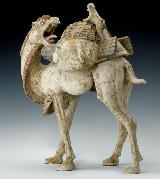 """""""A superbly modelled, painted pottery, figure of a standing camel. The camel with realistically modelled pose, head turning back with mouth open, attacking a playful monkey who is seated on the rear of the large pack which sits between the humps. This is a superb realistic portrayal of a heavily laden camel, an animal that was an important part of China's trading life along the Silk Road."""":"""