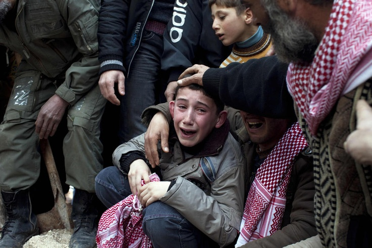 Crisis in Syria - Ahmed, center, mourns his father Abdulaziz Abu Ahmed Khrer, who was killed by a Syrian Army sniper, during his funeral in Idlib, north Syria, Thursday, March 8, 2012. (AP Photo/Rodrigo Abd)