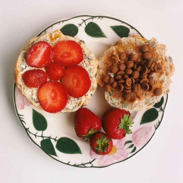 Bread with fruit and nuts. One half with soy butter and strawberries, the other half with peanutbutter and biscuit pieces. | Breakfast