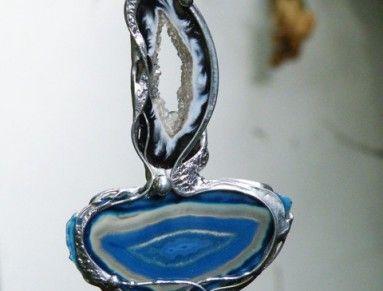 Autorský cínový šperk s velmi pěkným, barveným plátkem achátu a řezem peříčkového achátu top kvality...  Peříčkový achát má u okrajů černou barvu, střed je bílý s průzorem a čirými mini krystalky, velikost je 3,5 x 1,4cm. Plátek achátu má velikost 4,3 x 2,3cm, barva je v odstínech modré s pěknou kresbou. Kameny jsou usazeny v cínu - bez lepení, zdobeny cínovaným drátem a kuličkami cínu. Leštěno, povrchově ošetřeno. Celková velikost šperku je 6,2 x 5,5cm. Zavěšeno na černé kůži, délka je…