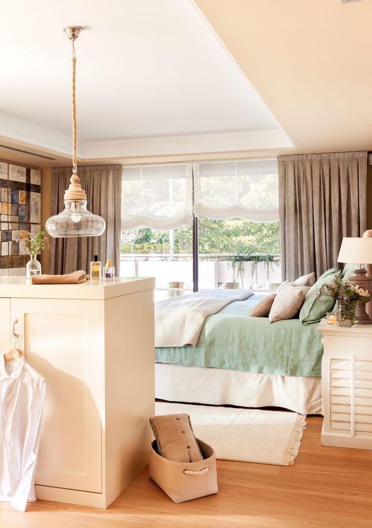 Dormitorio con mueble exento como parte de vestidor y lámpara colgando sobre el mueble 00427883