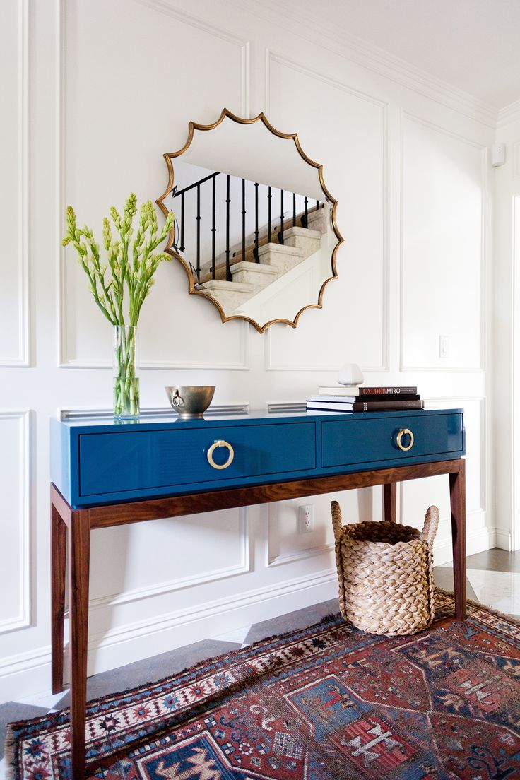 Blue console table in hallway of white home with geometric mirror and tall vase of flowers