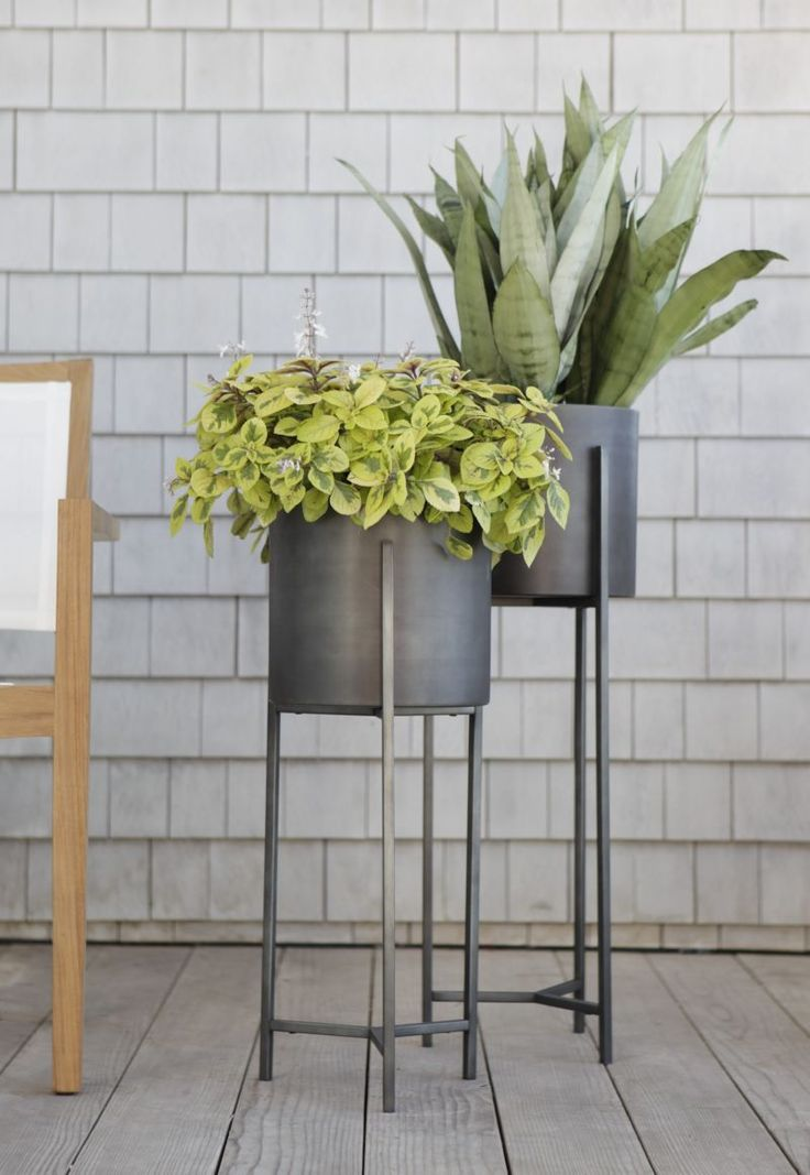 "Handcrafted iron planters with warm antiqued bronze finish are framed inside an architectural stand with slender legs and tripod crossbar supports. 100% ironAntique bronze finishAccommodates a 9"" pot (no drainage opening)For indoor or outdoor useMade in India."